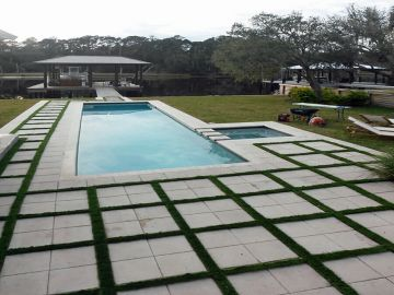 Swimming pool concrete pavers artificial grass fake synthetic turf pool house table blue water lounges chairs square stones
