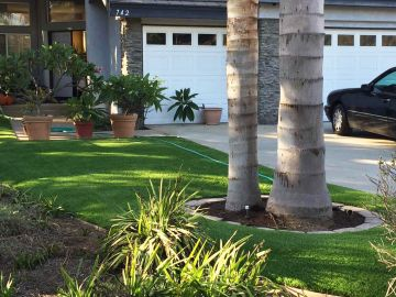 Front yard landscaping ideas landscape lawn artificial grass, synthetic turf, garden flowers palm trees, garage door, driveway