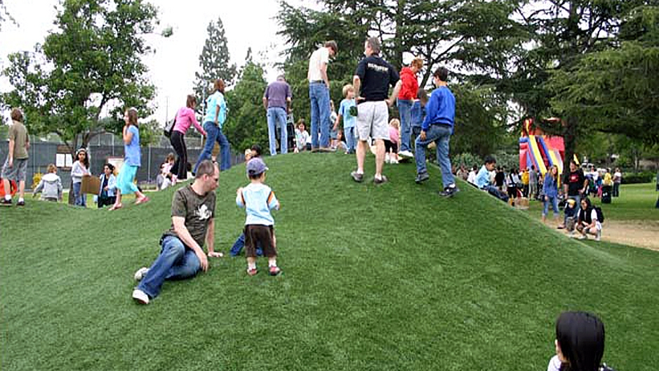 Public park artificial grass synthetic turf children parents green hill sit play on grass comfortable play area for small kids