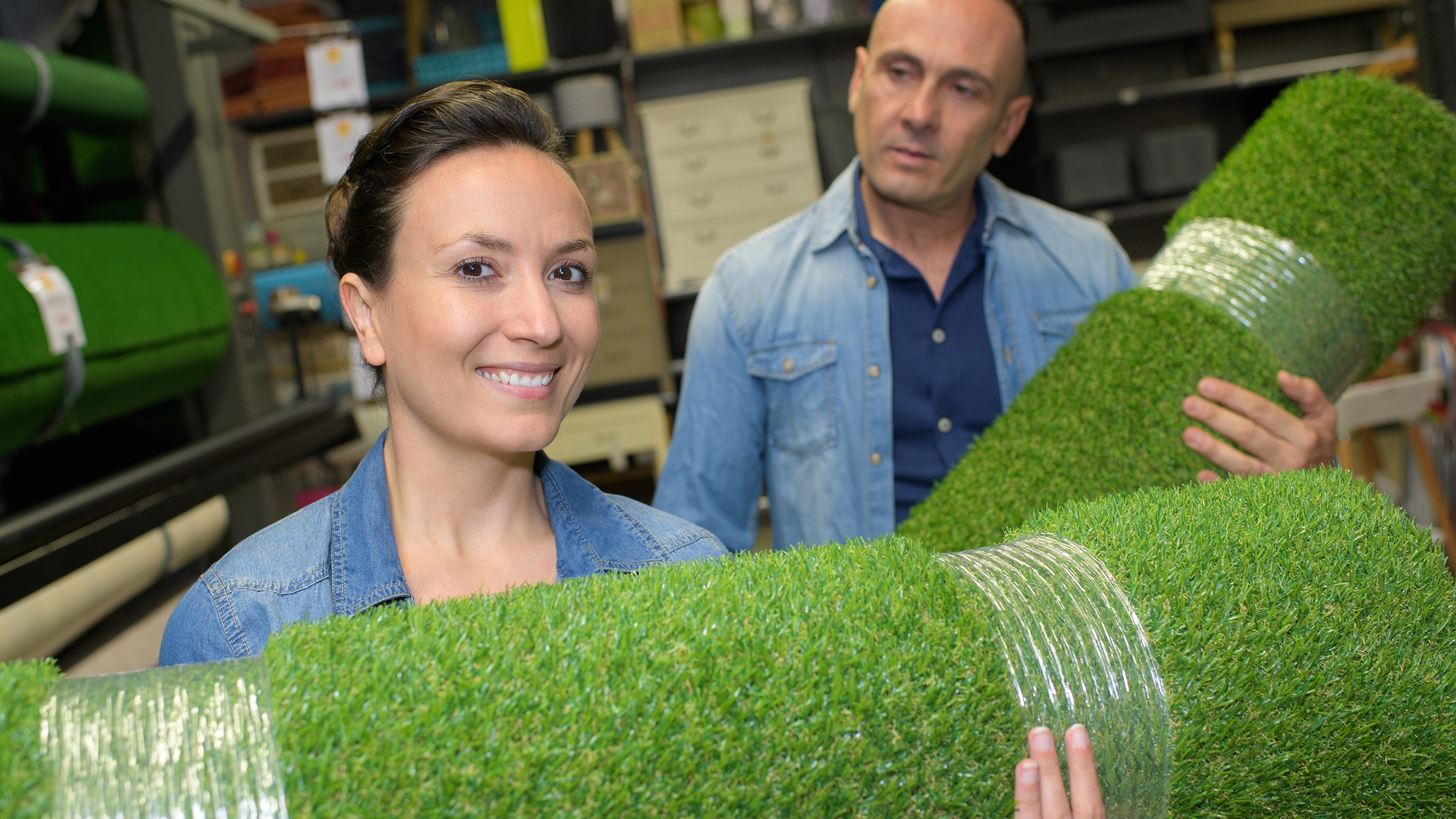 Man women holding rolls of artificial grass