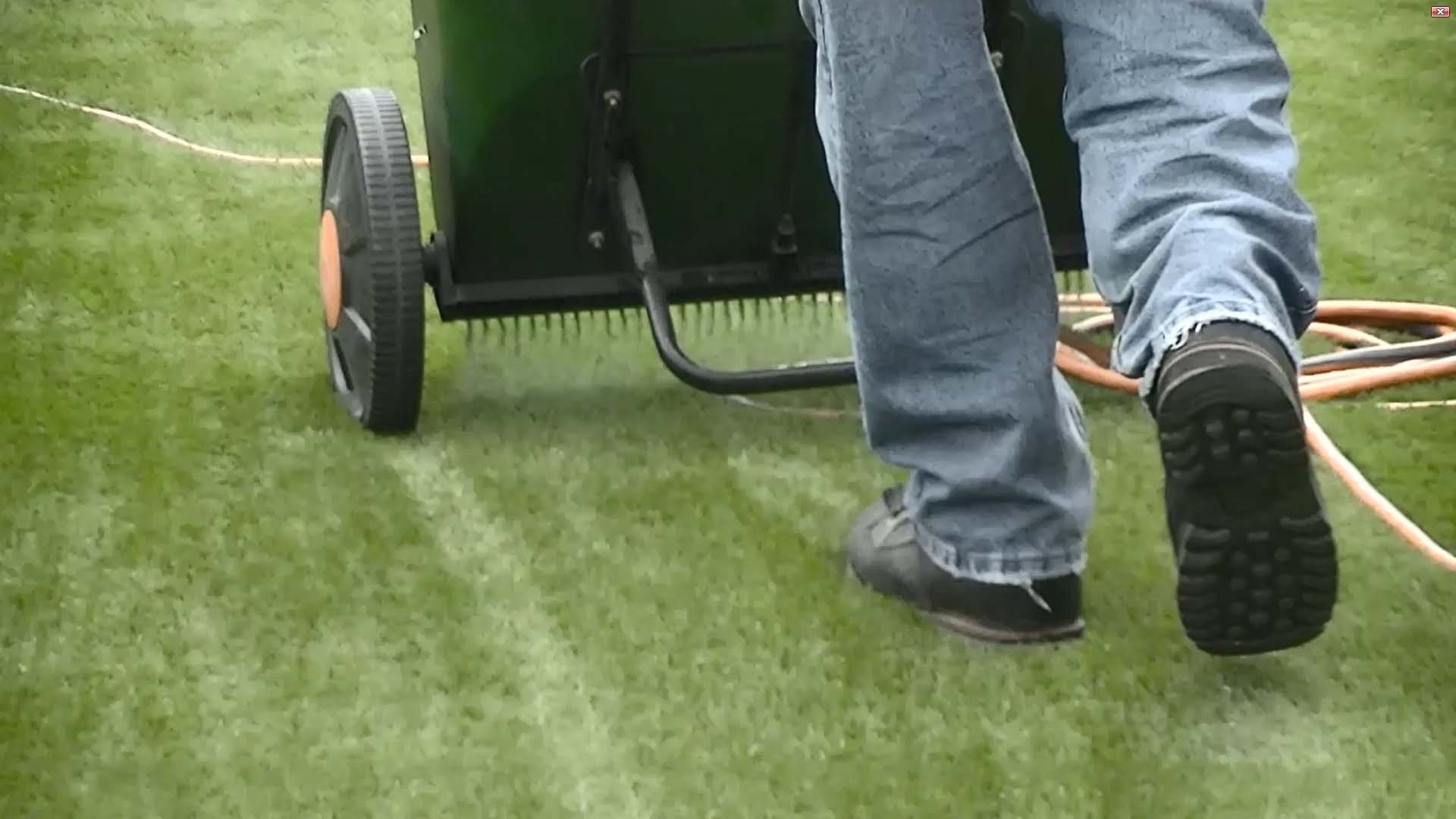synthetic artificial grass installation man walking infilling turf