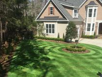 Front yard landscape with striped Global Syn-Turf Spring-50 artificial grass, round flower bed, two-story house.