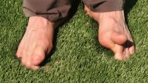 Bare feet of artificial grass green synthetic turf