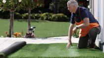 man laying down artificial grass on a patio