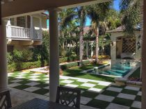 Patio deck design ideas. Swimming pool palm trees artificial grass chess checkered concrete backyard, covered porch.