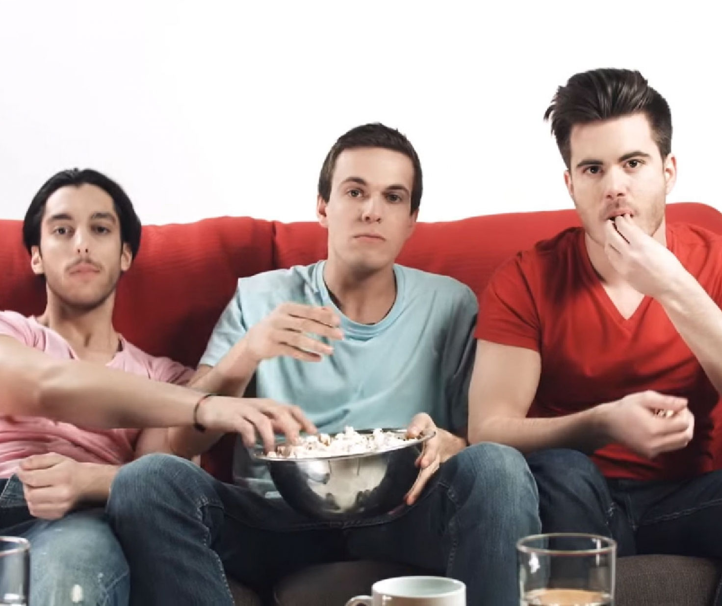 Three young man eat popcorn red counch