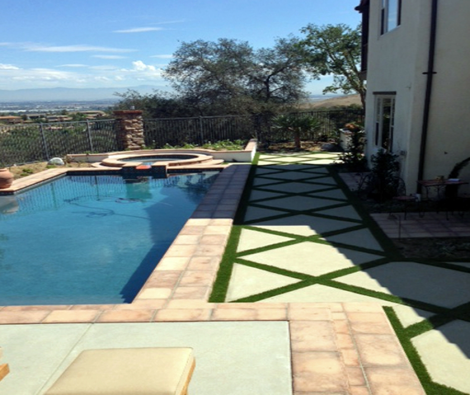 Artificial grass installed between pavers by swimming pool synthetic turf installation
