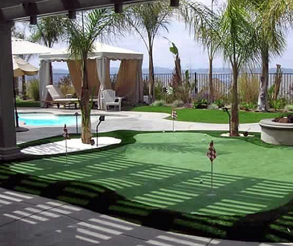 Golf putting green practice by swimming pool ocean palm tresses gazebo green hotel backyard artificial grass synthetic green turf lawn