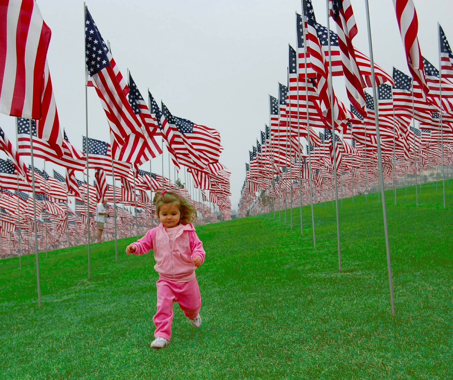 child pink girl American flags runs artificial grass