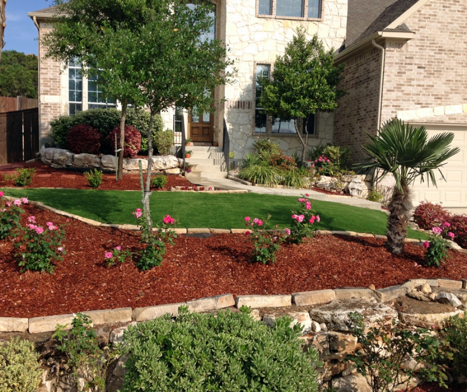 Front Yard with mulch, roses, palm tree, natural stone borders, brick house, decorative bushes