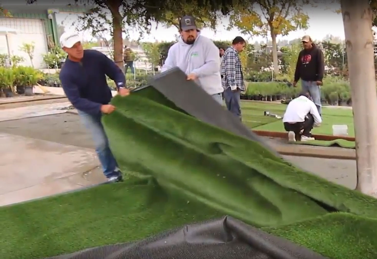 Installing synthetic grass pulling turf roll