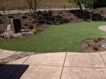 Synthetic turf green backyard stones square pavers landscaping ideas landscape lawn flowers fake artificial grass