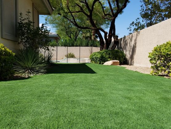 Backyard synthetic lawn artificial grass installation green landscape with shrubs by stone fence Riviera Monterey 50 M Blade shape blades