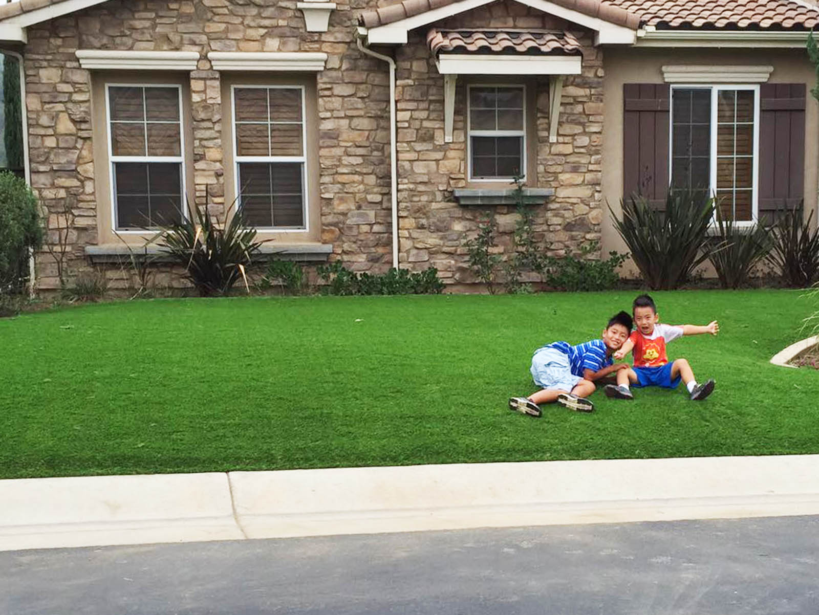 Artificial grass synthetic turf drought water children front yard playing two boys summer green grass lawn gray stone house