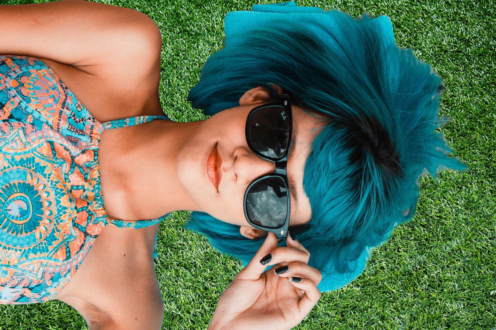 Beautiful woman in dark glasses with blue hair on artificial grass relax