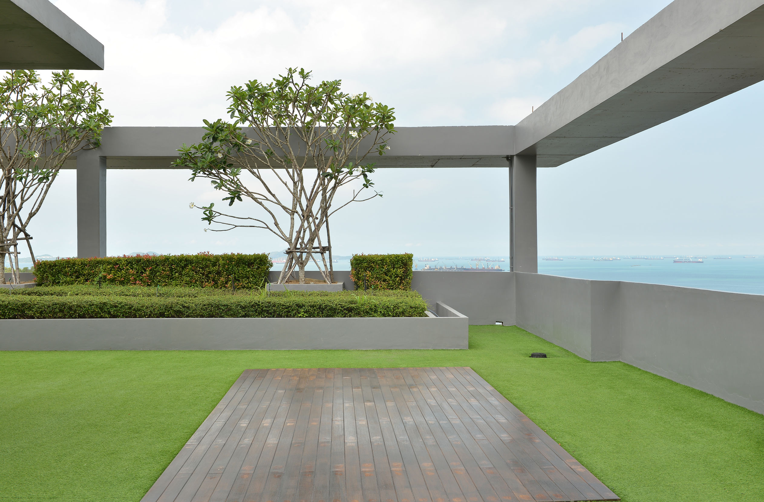 Artificial grass, synthetic turf installation on a rooftop, rooftop garden, trees, ocean