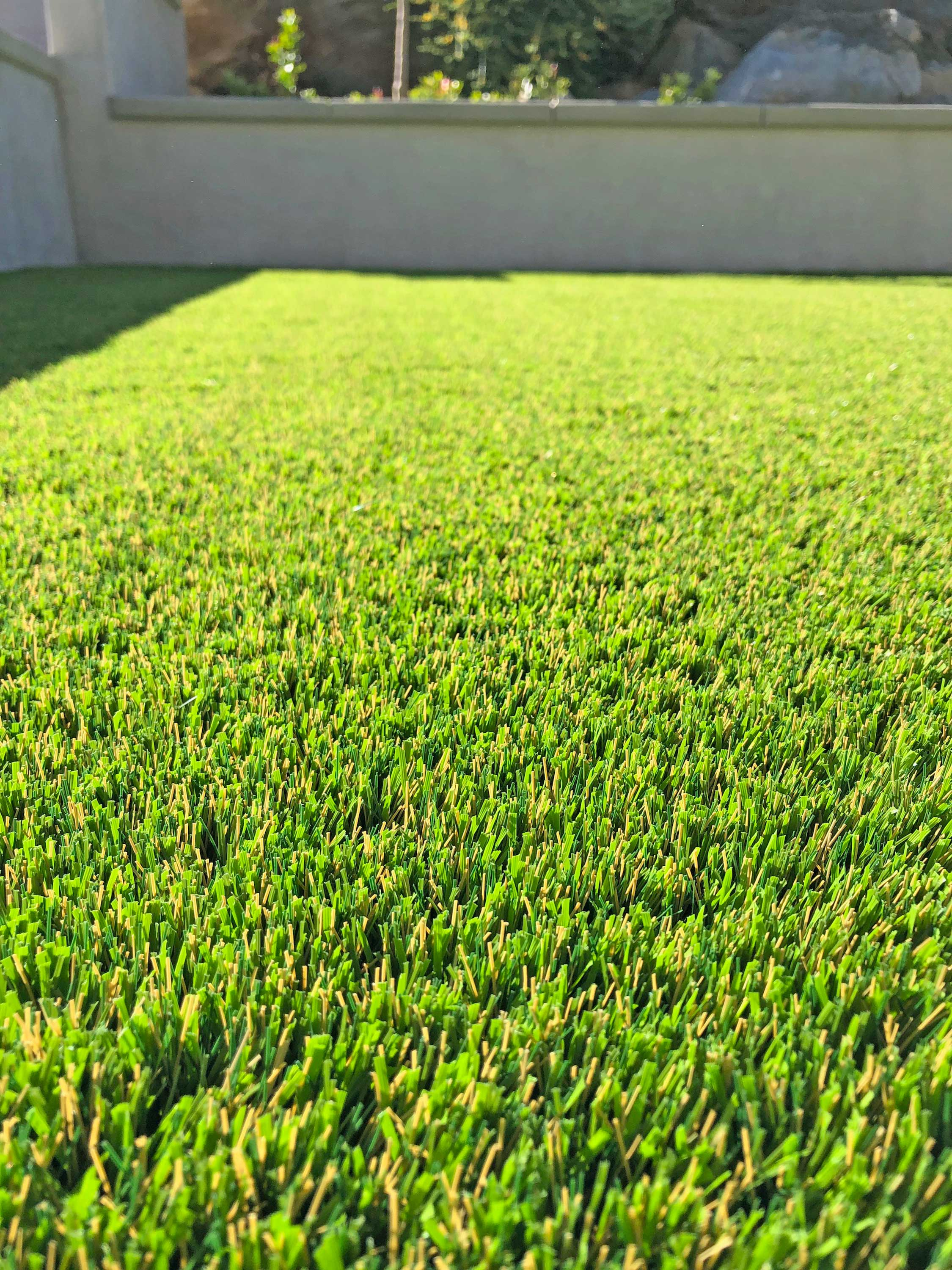 Backyard with Natural Stone Featuring Synthetic Grass