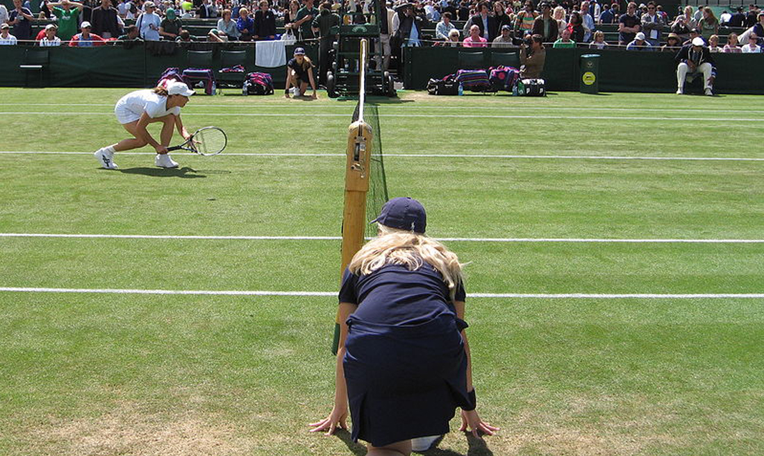 Wimbledon grass court with players and ball girl